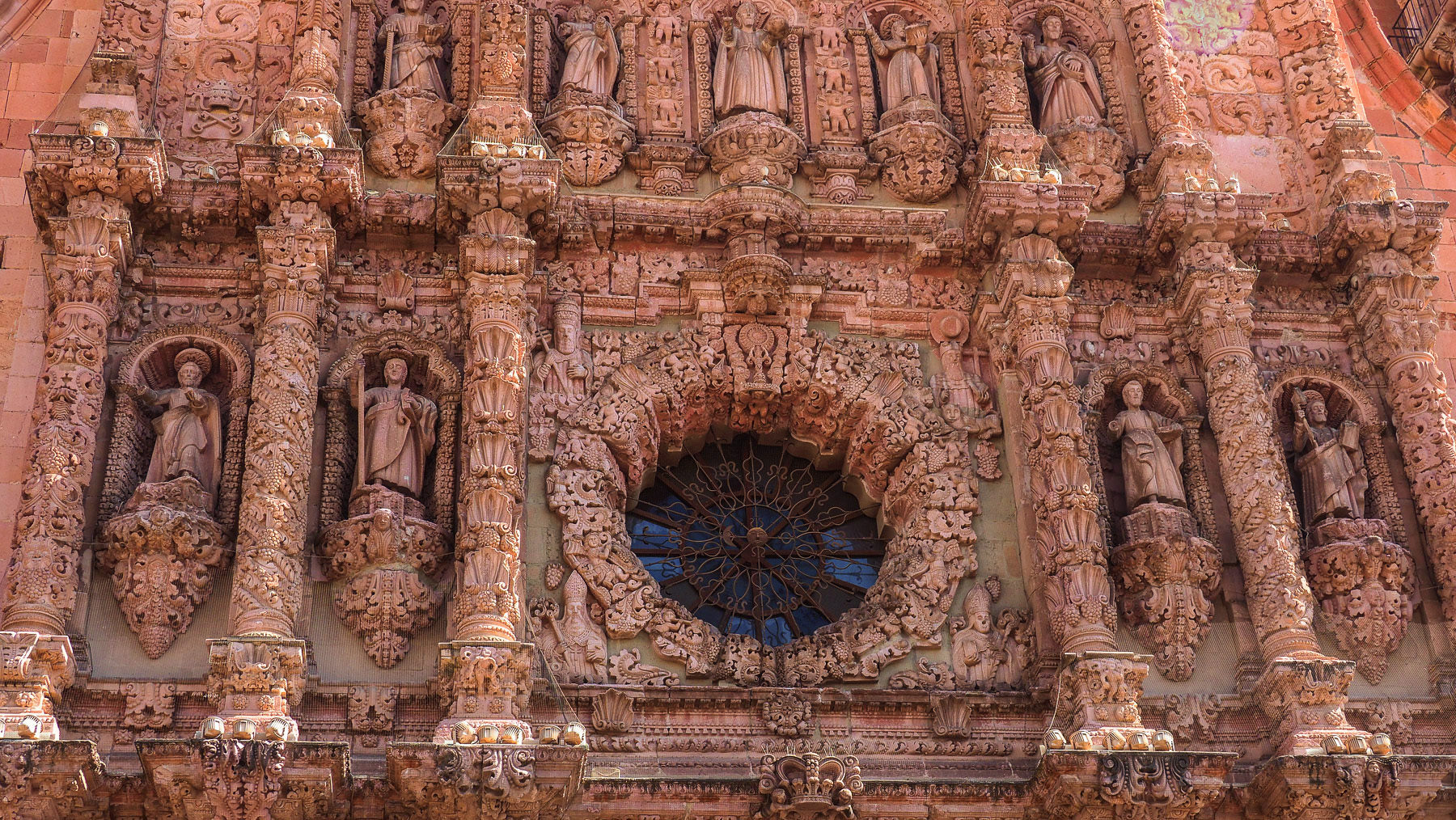 Detailreiche Hauptfassade in rosafarbenem Stein