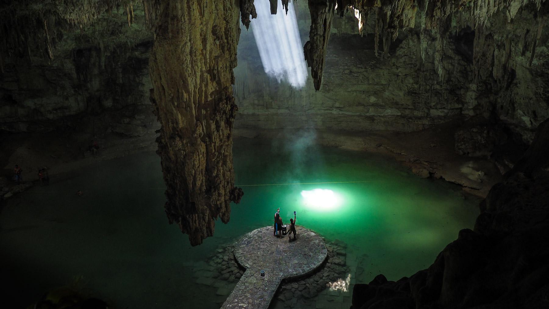 Ein einsamer Sonnenstrahl wird sichtbar im Weihrauch der Maya Tänzer in der Cenote Suytun.