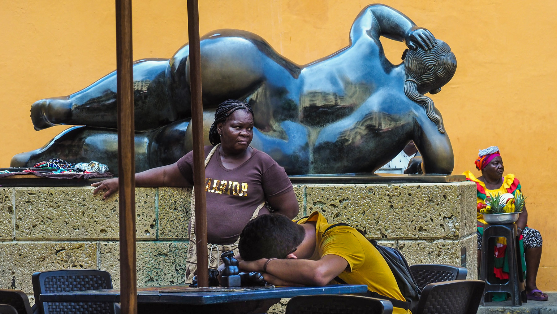 Wenig los im heißen Catagena – Straßenverkäufer dösen neben einer Figur von Botero