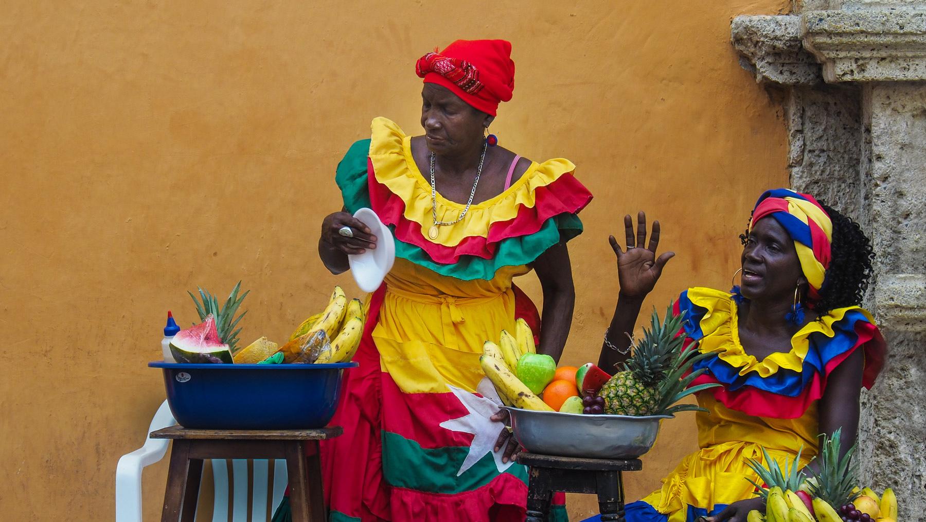 Fotogene farbenfroh gekleidete Obstverkäuferinnen warten auf Kundschaft