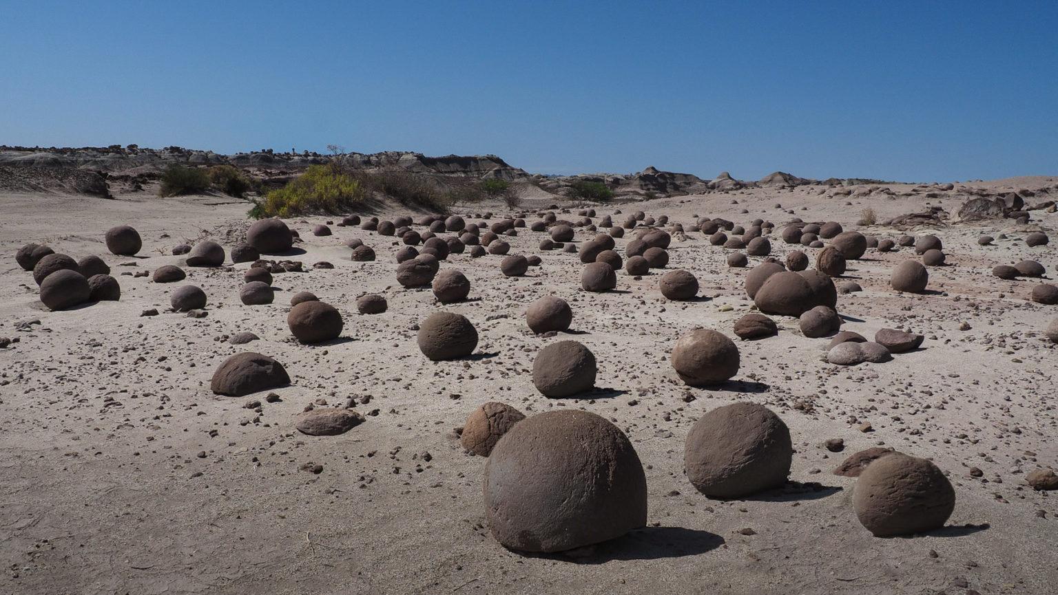 Merkwürdige Ebene mit perfekt runden schwarzen Steinen