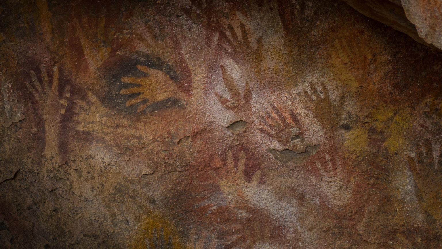 Fußabdruck eines Nandus inmitten vieler Hände