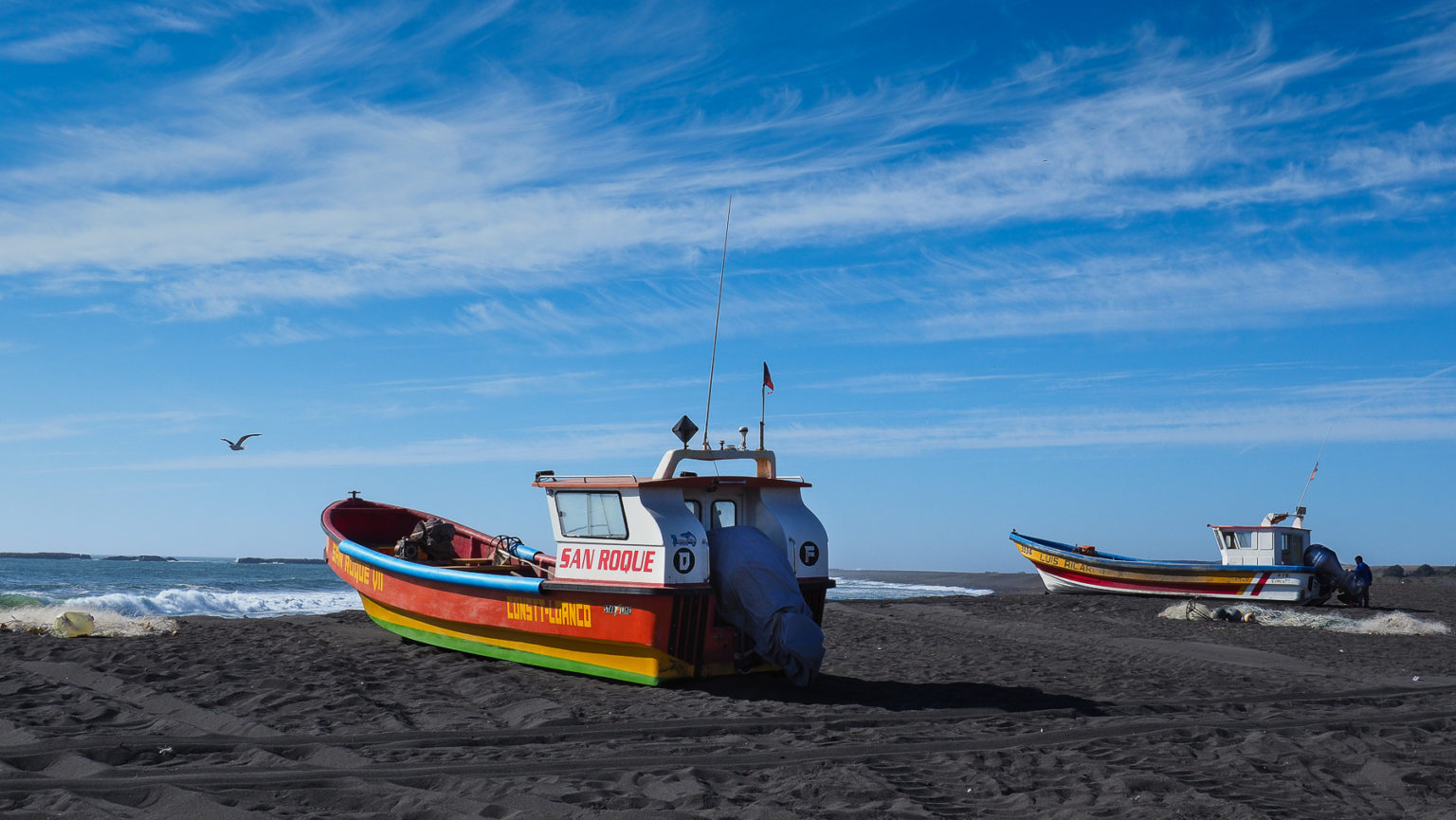 Bunte Fischerboote auf schwarzem Lavastrand